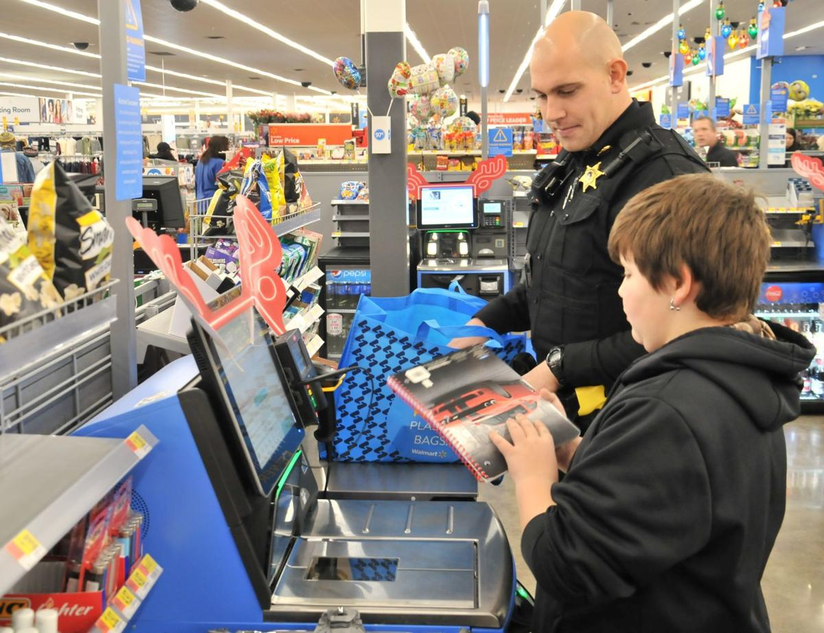James Button, 12, and Cayuga County Sheriff's Office Deputy Cody Forgham check out items during the Shop With A Cop event at Walmart in Auburn Saturday.