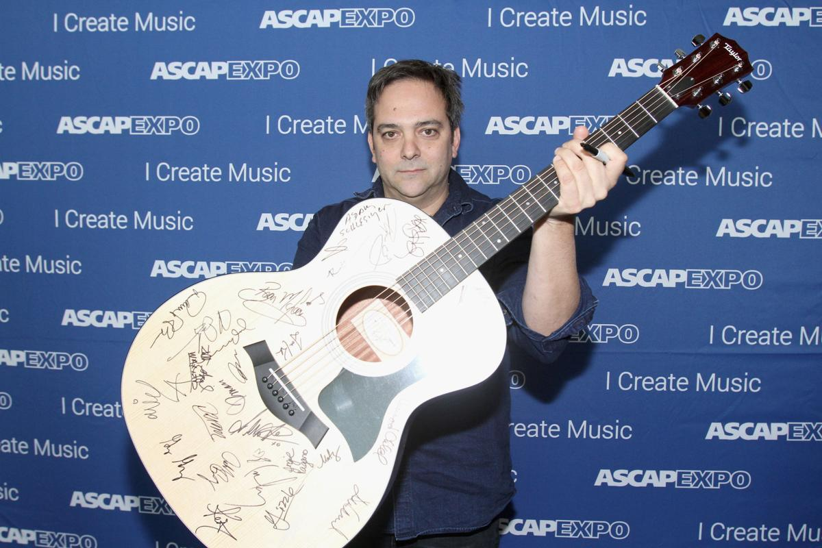 """Composer Adam Schlesinger poses with a #StandWithSongwriters guitar, which will be presented in May to members of Congress to urge them to support reform of outdated music licensing laws, during the 2016 ASCAP """"I Create Music"""" EXPO on April 30, 2016 in Los Angeles. Schlesinger is in an upstate New York hospital battling the coronavirus."""