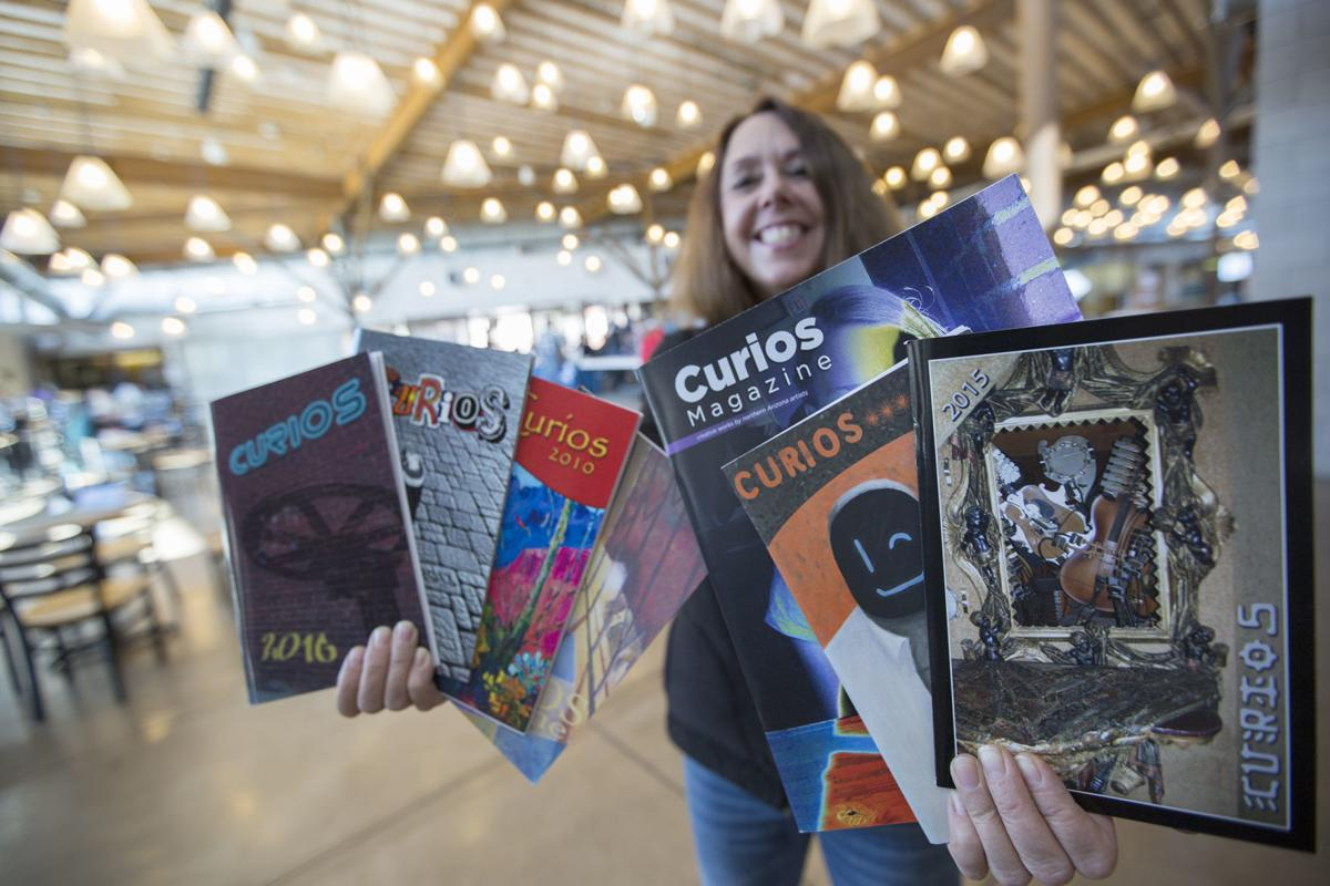 Coconino Community College English Instructor Sandrah Dihlmann holds past copies of Curios literary magazine, which features work by northern Arizona artists and writers..jpg
