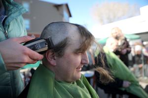 Dozens of people shave their heads in name of childhood cancer research