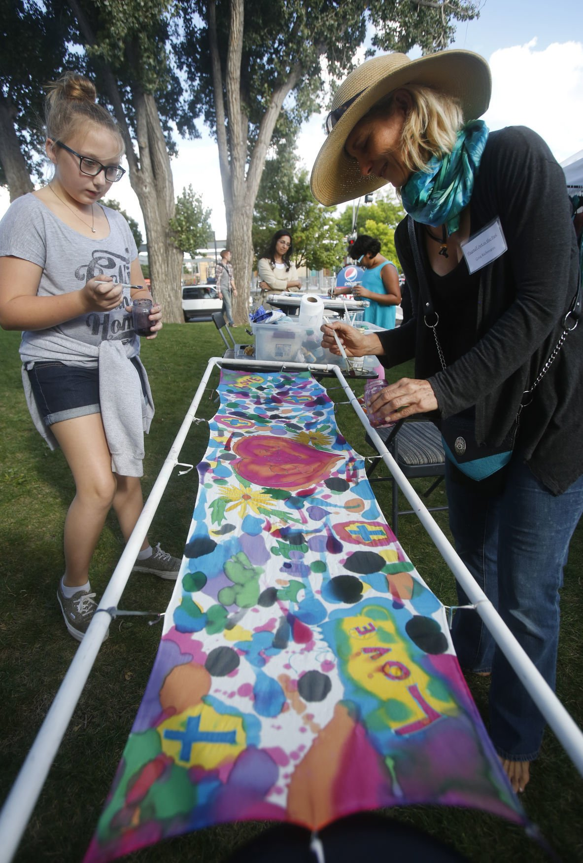 Artist Gina Richman, right, paints on a large piece of silk with Kenna Moore, 12, left, during Art in the Park Saturday afternoon at Wheeler Park. 2016. taylor.jpg