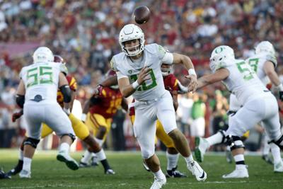 Oregon quarterback Justin Herbert (10) chases after a bad snap, leading to a sack against USC at the Los Angeles Coliseum on November 5, 2016.