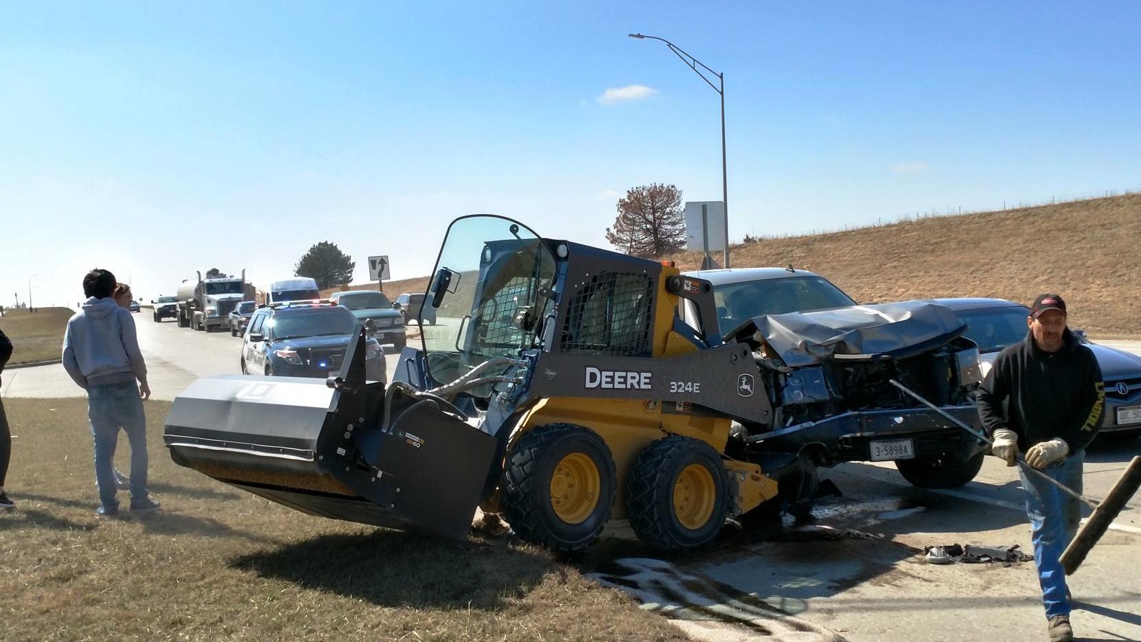 Truck hits skidloader on highway