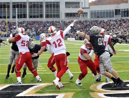 58a7d8615 Western Kentucky quarterback Brandon Doughty (12) throws as pass while  being pressured by Army s Robert Kough (99) during the first half of an NCAA  college ...