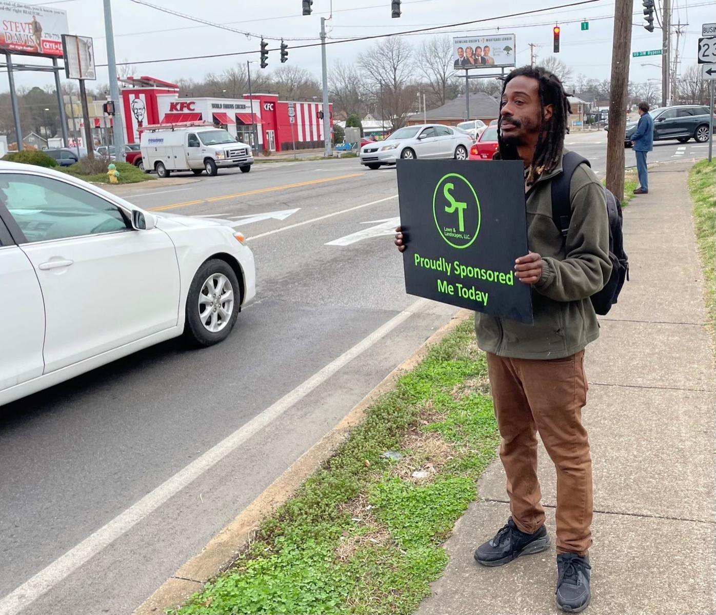 Sign of the times: Homeless 'fly signs' for sponsor businesses