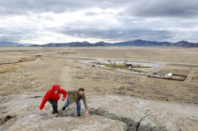 David Turner and his son Jared climb to the top of Independence Rock
