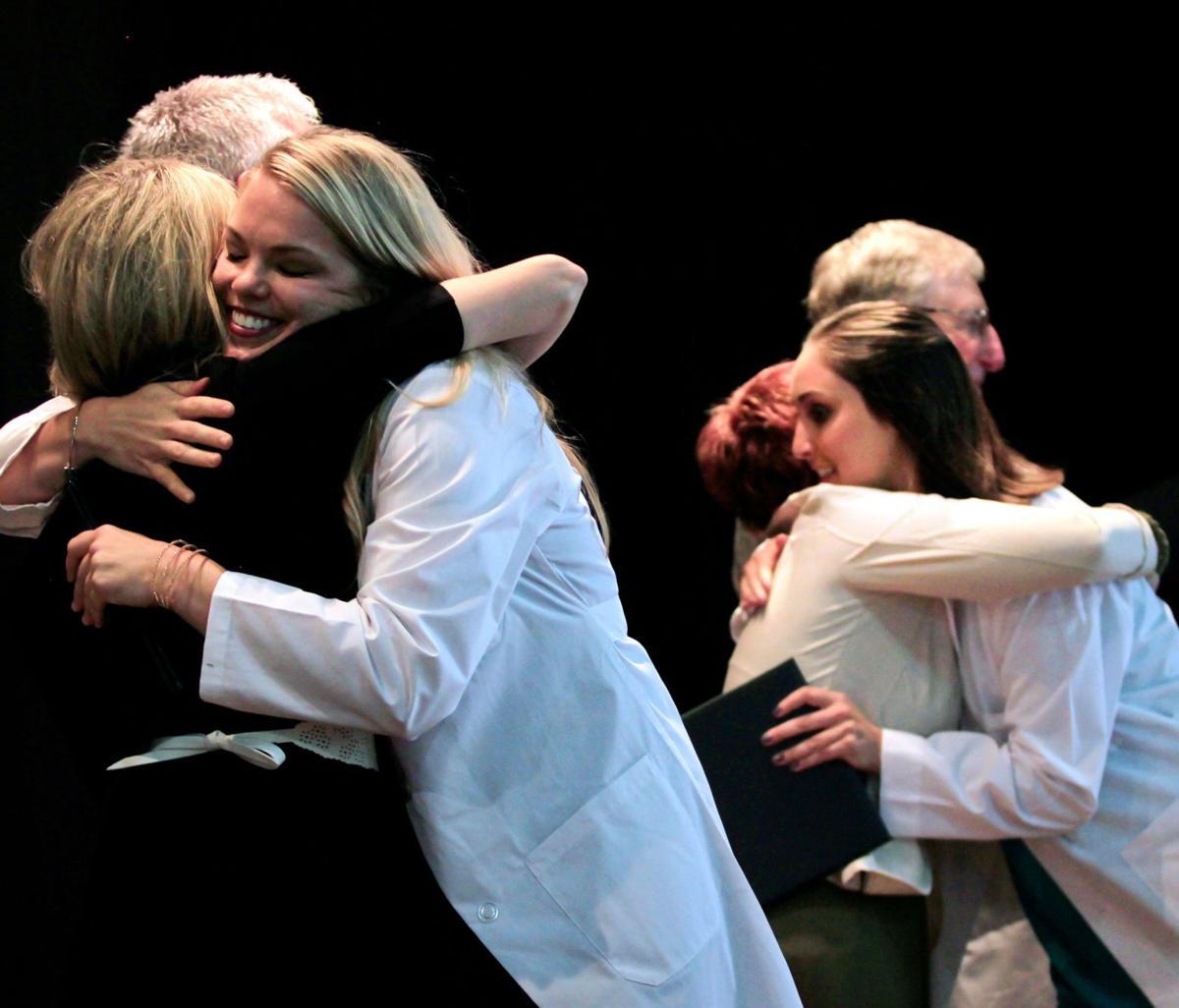 Monica and Laurene hug their professors