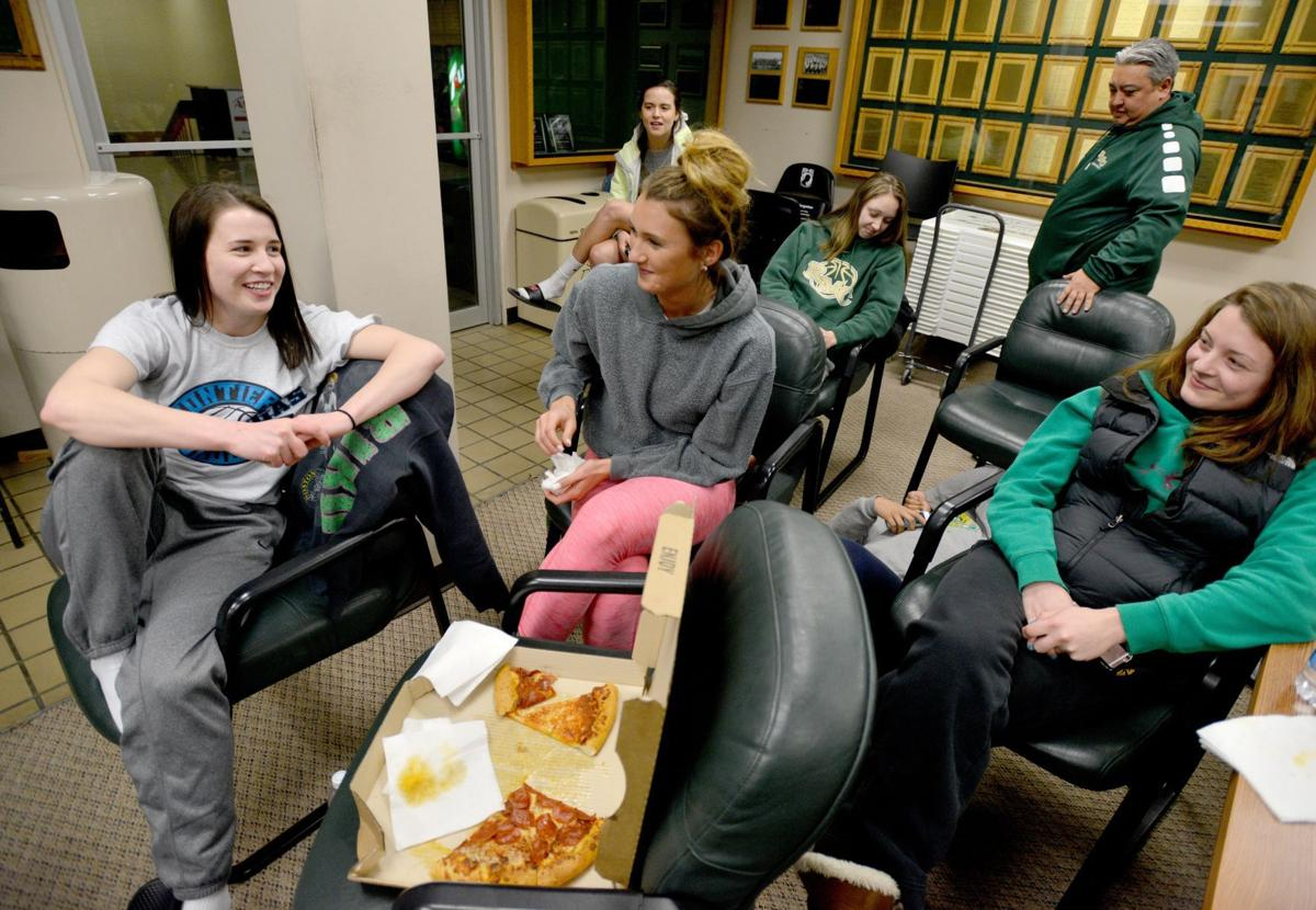 Rocky Mountain College players chat and eat pizza
