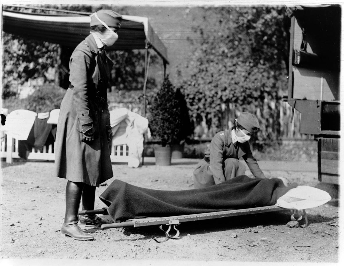 Two Red Cross nurses with person on stretcher