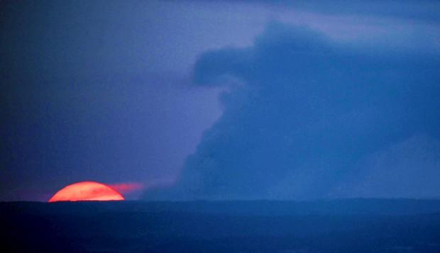 The sun sets behind a column of smoke