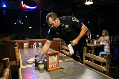 Undersheriff Kevin Evans wipes a table