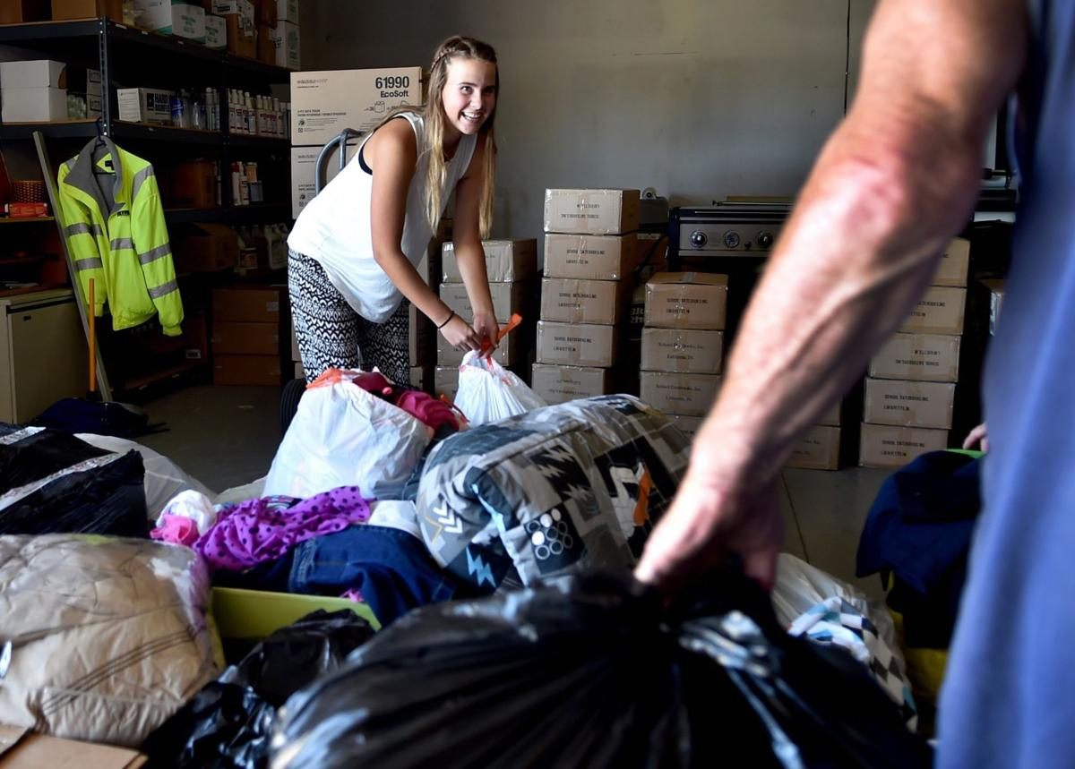 Addie Nielsen picks up bags of donated clothes