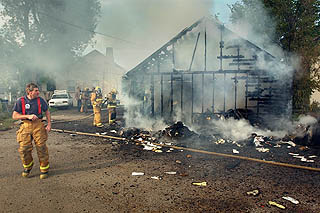Trash fire damages garage, may be arson