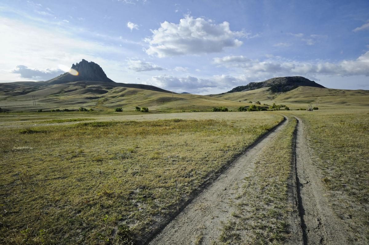 A two-track road winds through the conservation easement between Birdtail Butte, left, and Lionshead Butte.