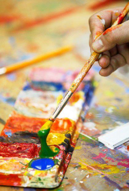 Carl Kershner dips his brush in paint