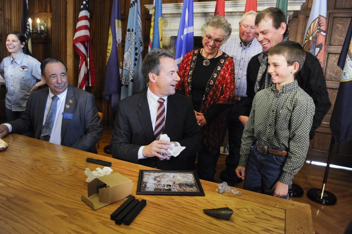 Luke Phipps, 12, right, gives Gov. Steve Bullock fossils