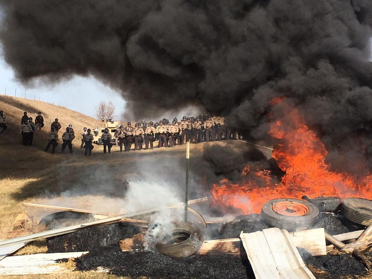 Tires burn as armed soldiers and law enforcement officers stand in formation