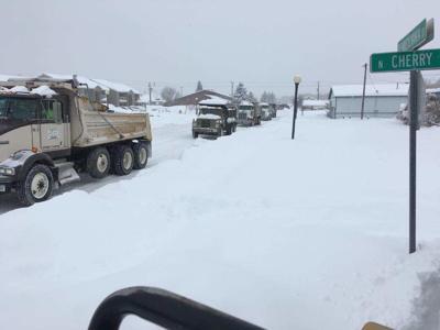 Dump trucks moving snow in Anaconda