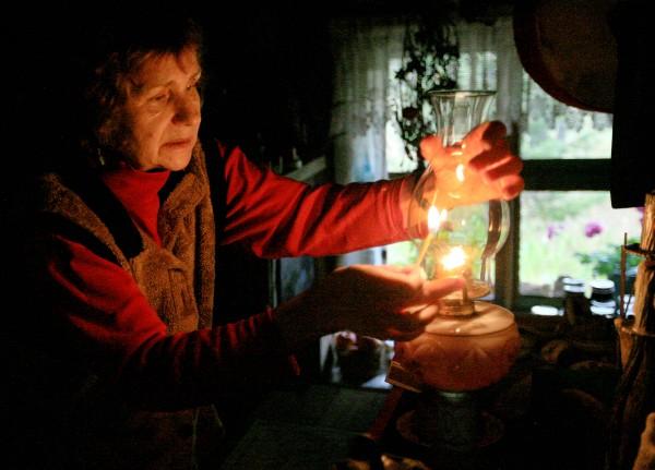 Jacqueline Mercenier lights a kerosene lamp