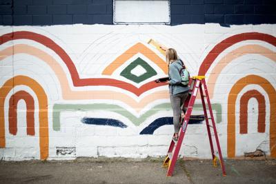 Molly Schiltz paints a mural on The Pub Station