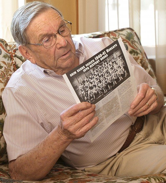 George Wallis looks at article about his college football team