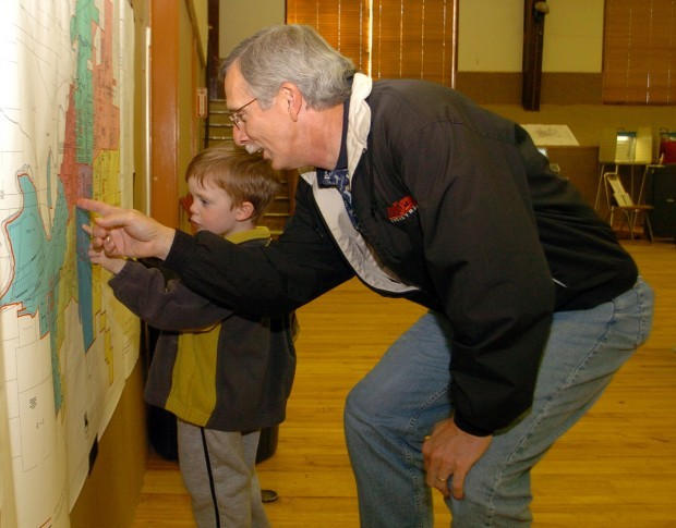 Jeb Beacham and grandson Taylor consult a map of voting precincts