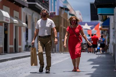 Tourists wearing a face masks walk down a street in Old San Juan, Puerto Rico on July 20, 2020. Puerto Rico Gov. Wanda Vazquez Garced issued a mandate to wear face masks in all public places to prevent the spread of COVID-19 amidst a spike of positive cases in the island.