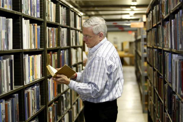 Library Director Bill Cochran looks at a book