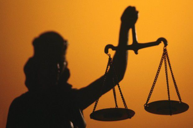 Illustration: Lady Justice holds scales