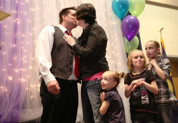 Ryan Carroll gets a pin and a kiss from his wife, Cressida