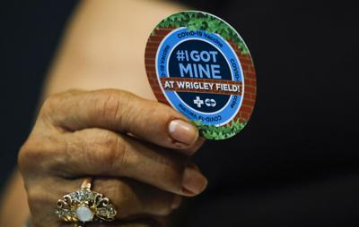 Eustorgia Alcarav, 72, holds a sticker after she received the first dose of the Pfizer COVID-19 vaccine at the American Airlines Conference at Wrigley Field on Monday, April 5, 2021.
