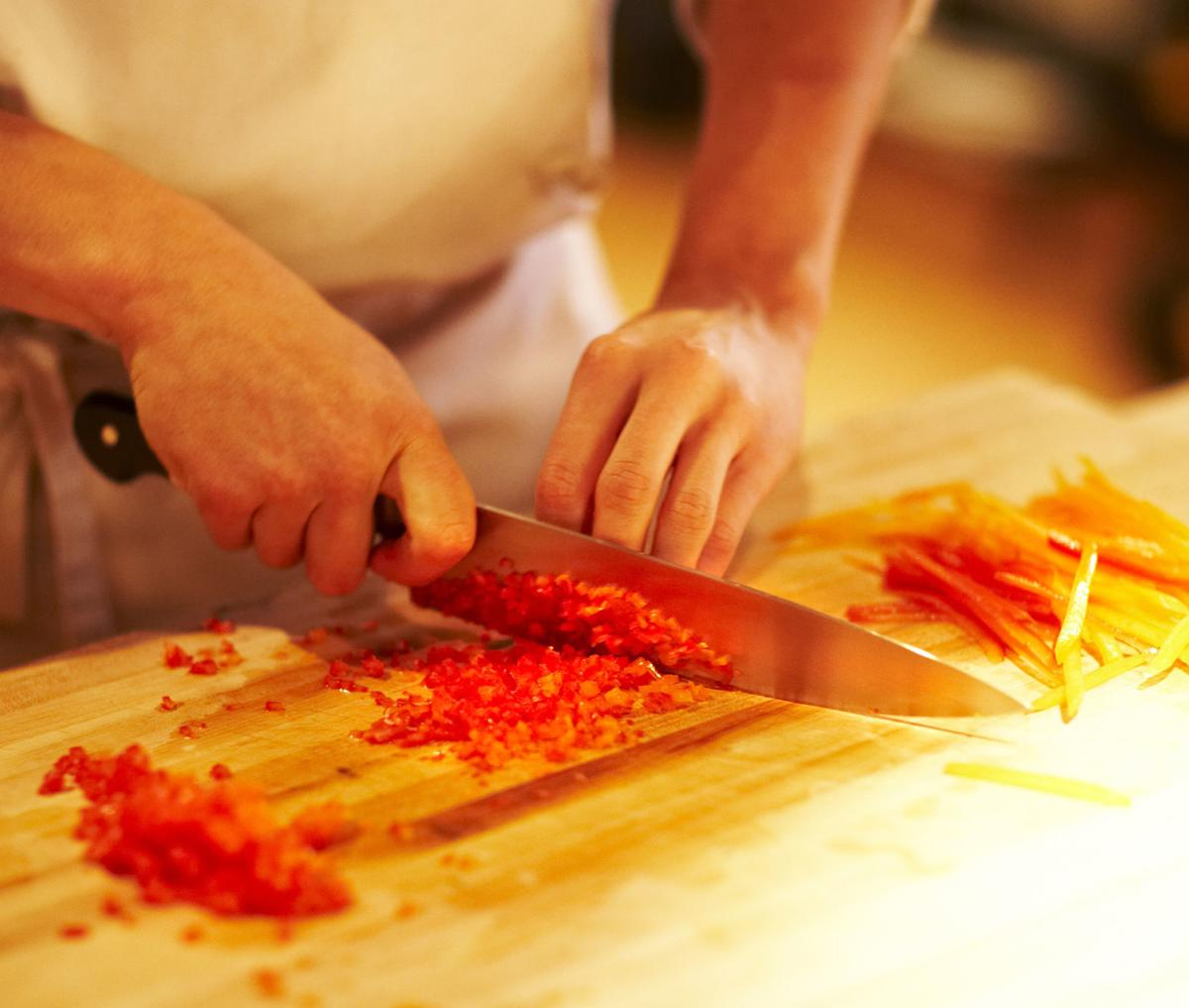 Chef mincing bell peppers with knife