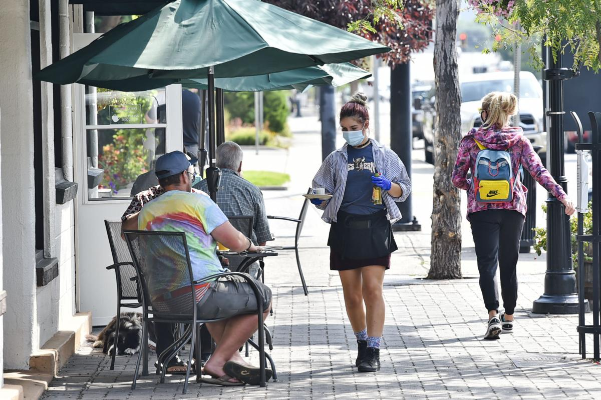 A masked waitress serves drinks and food outside the Western Cafe in Bozeman on Thursday, August 27, 2020.