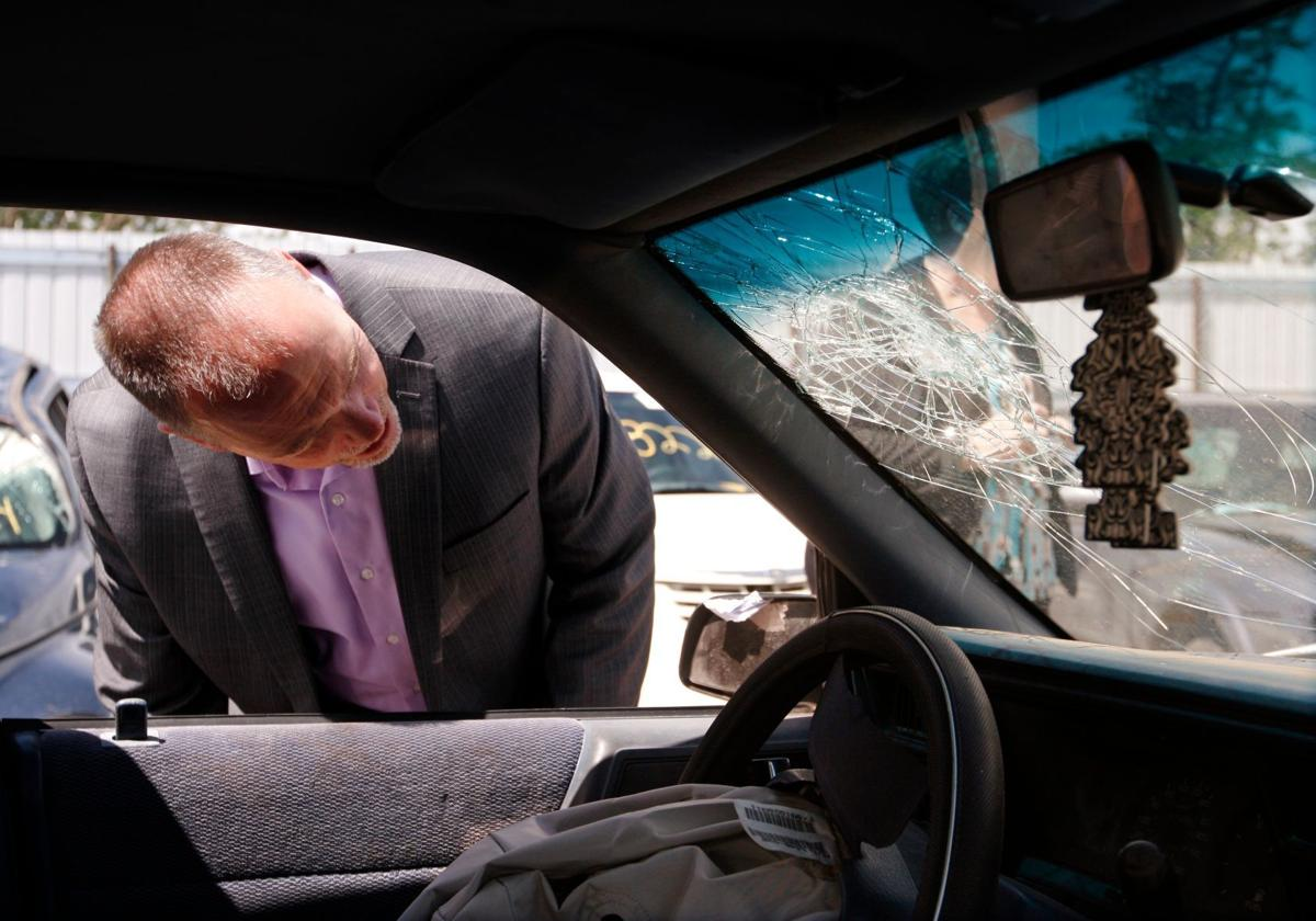 Mike Tooley looks at damage to a windshield
