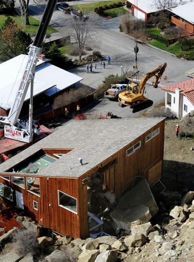 A 350-ton crane lifts a track hoe into position