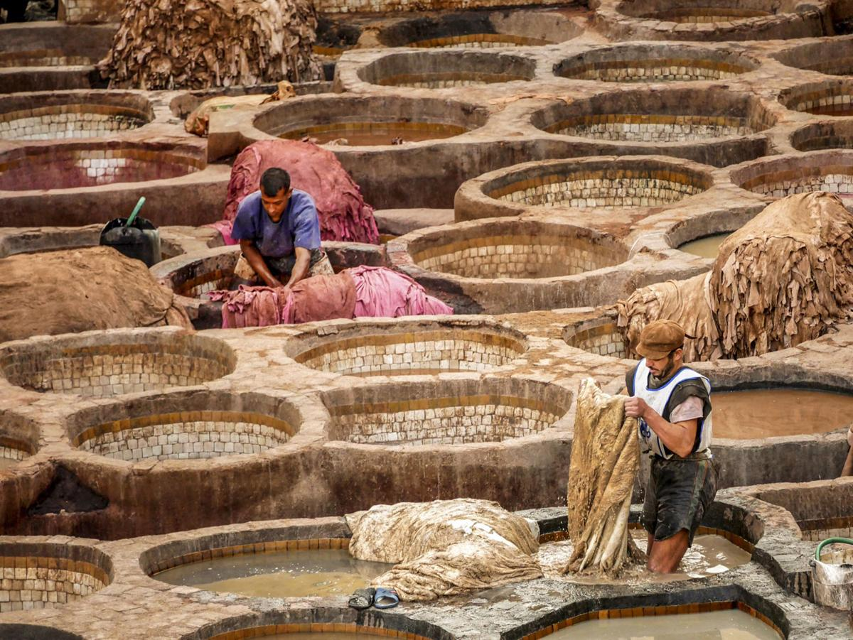 Two men wash and dye camel, goat, sheep and cow hides in the Chouara, the 11th Century tanners' quarter. Pigments are from plants and minerals.