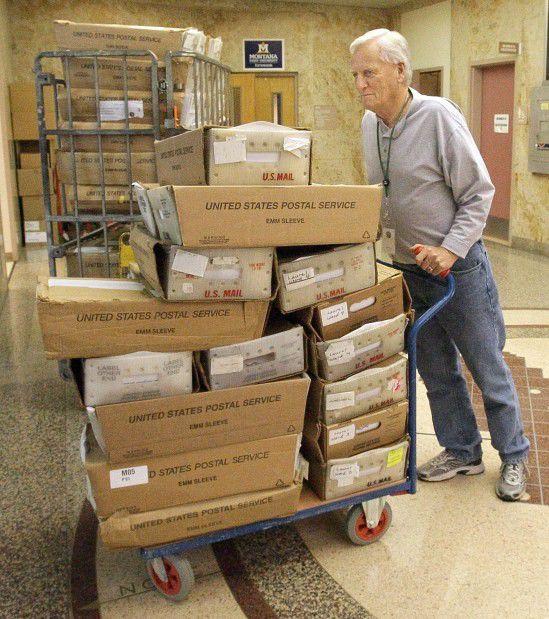 Dean Idstrom wheels a cart full of election ballots