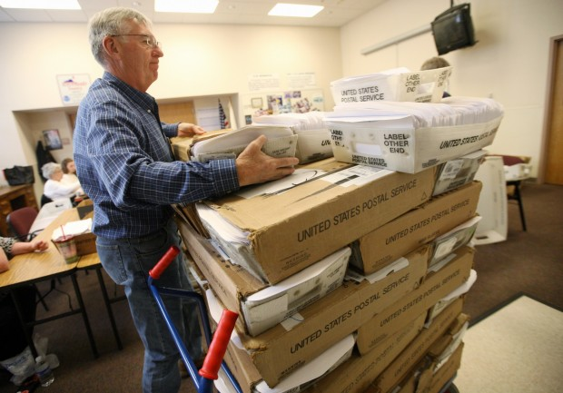 Stephen Sylvester stacks boxes of ballots