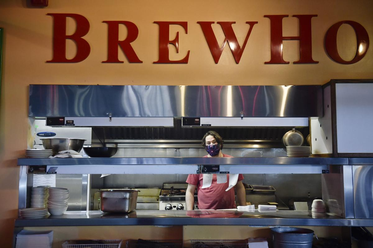 A cook at Brewhouse Pub and Grille checks on a food order