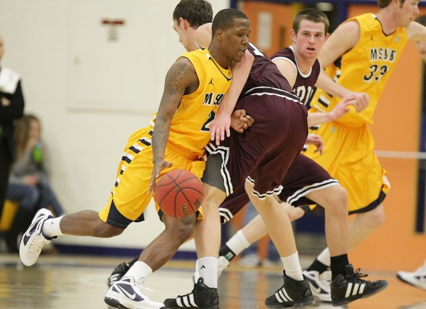 Antoine Proctor of Montana State Billings runs into Andy Poling