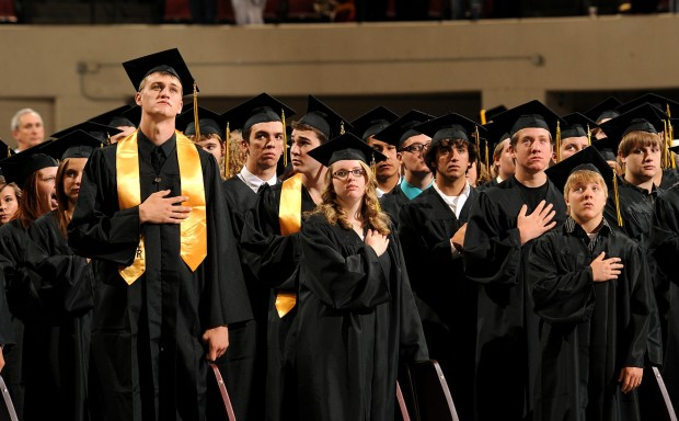 Graduates stand for the National Anthem