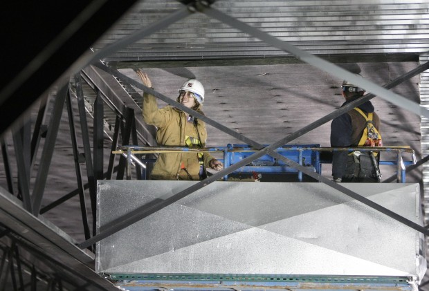 Two workers inside the Rimrock Auto Arena at MetraPark install a sheet of acoustic paneling