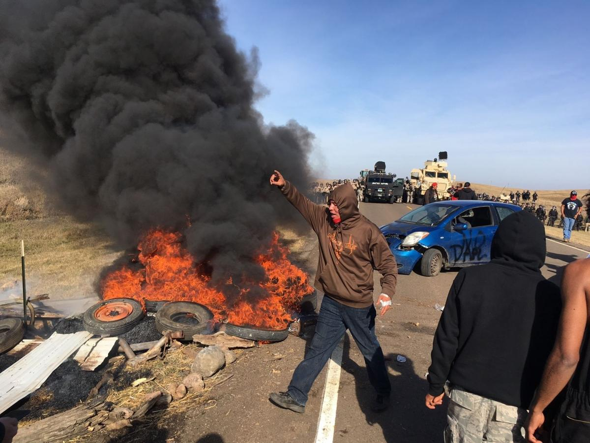 Demonstrators stand next to burning tires