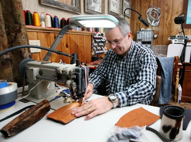Tim Trafford sews the zipper on a cowhide bottle koozie