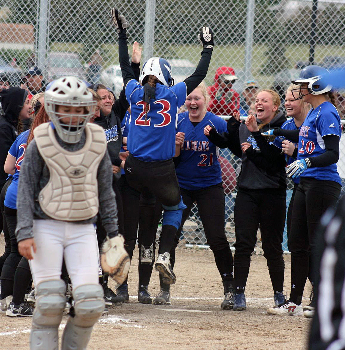 Teammates welcome Peyton Kehr (23) at home plate