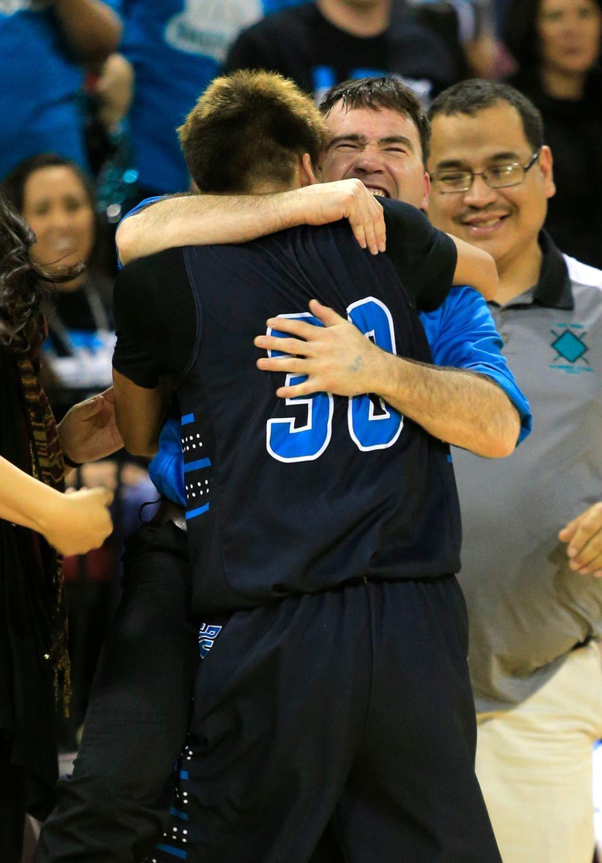 Lame Deer's Draven Hart hugs his coach Allen Fisher