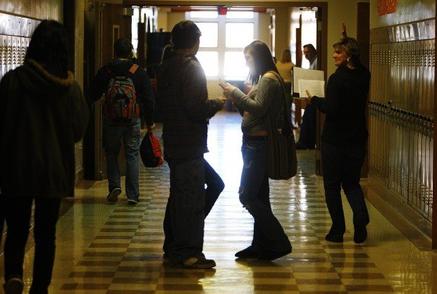 Students and faculty walk through a second-floor hallway