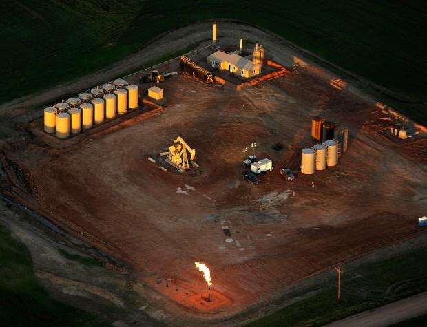The sun rises on an oil well