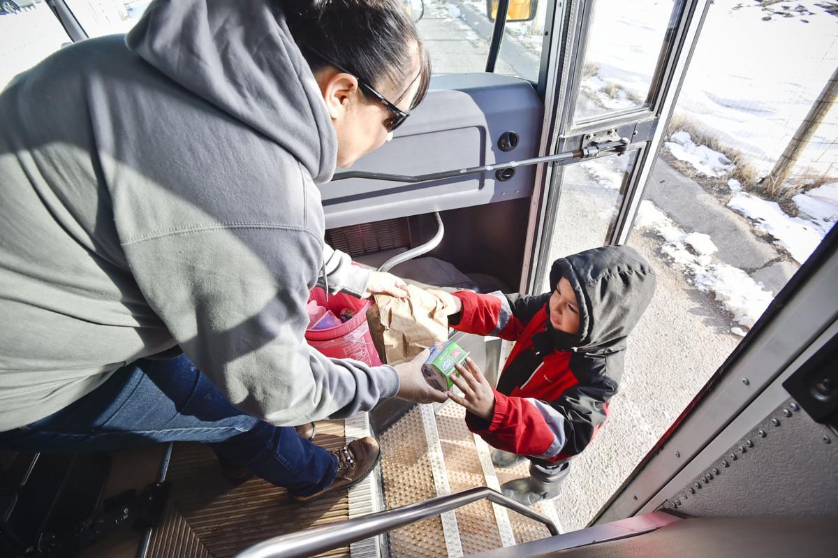 Nicklo Crossguns hands a young boy a sack breakfast