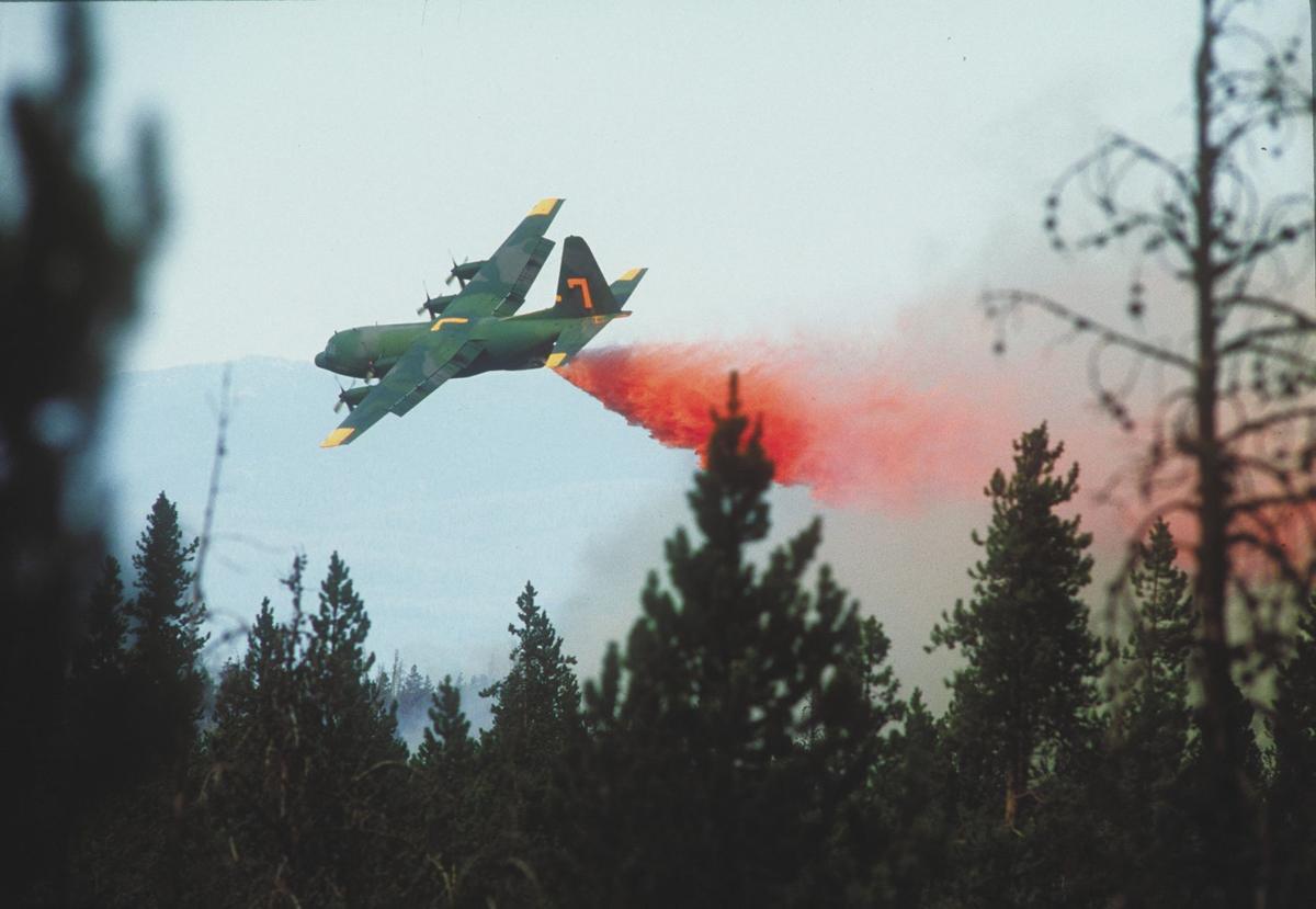 A C-130 drops retardant